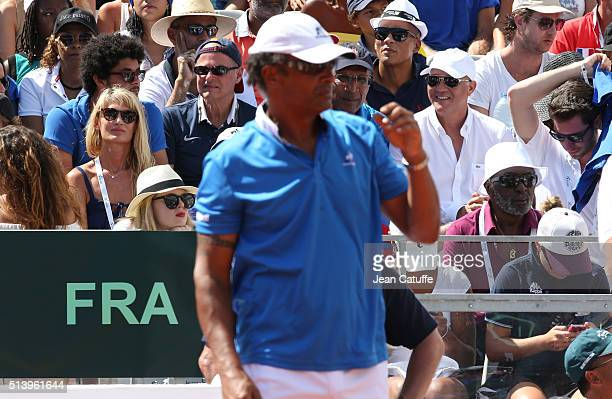 Isabelle Camus wife of Yannick Noah and Zacharie Noah his father look on while Yannick Noah stands on the court as captain of Team France during day...