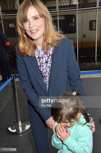 Isabelle Carre poses with a little smurf admirer during the 'Global Smurfs Day' Ceremony At the Gare Du Nord on June 22 2013 in Paris France