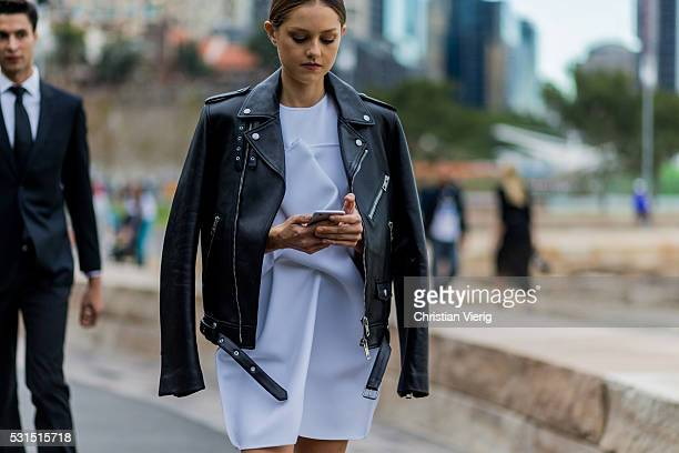 Isabelle Cornish wearing a white Toni Maticevski dress a black Burberry leather jacket while writing a text message on her phone outside Toni...