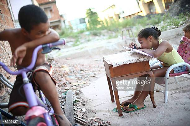 Isabelle da Costa de Sousa who contracted Dengue fever twice sits at a makeshift desk in the rubble of a former home next to construction in the...