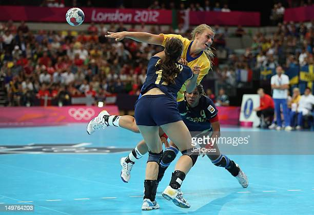 Isabelle Gullden of Sweden passes the ball while defended by Elisabeth Pinedo Saenz and Marta Mangue Gonzalez of Spain during the Women's Handball...