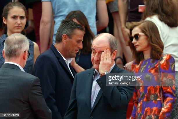 Isabelle Huppert looks on as President of the Cannes Film Festival Pierre Lescure puts his hand to his head before a minute of silence is held for...