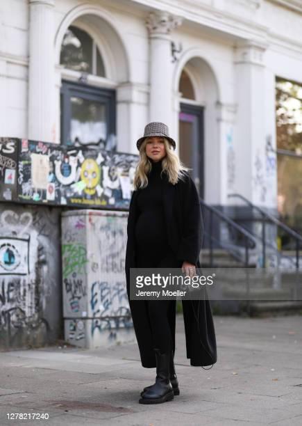 Isabelle Schroeder wearing Dior bucket hat, Bottega Veneta boots and mini pouch, Joseph coat, black turtleneck and The Mama Set leggings on October...