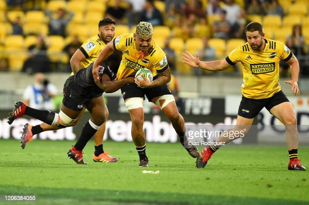 Isaia WalkerLeawere of the Hurricanes carries the ball with Dane Coles of the Hurricanes and Vince Aso of the Hurricanes in support during the round...