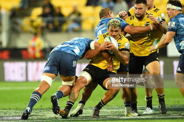 Isaia Walker-Leawere of the Hurricanes gets tackled during the round six Super Rugby match between the Hurricanes and the Blues at Westpac Stadium on...