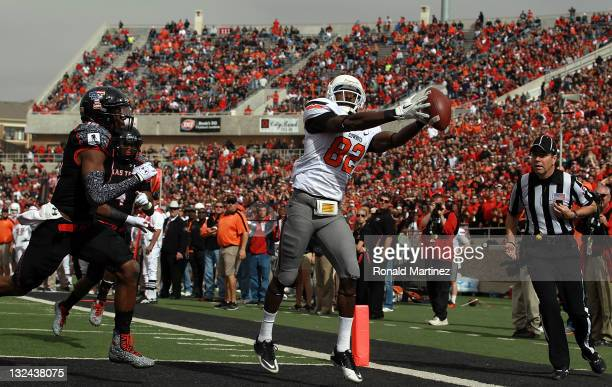 Isaiah Anderson of the Oklahoma State Cowboys makes a touchdown pass against DJ Johnson of the Texas Tech Red Raiders at Jones ATT Stadium on...