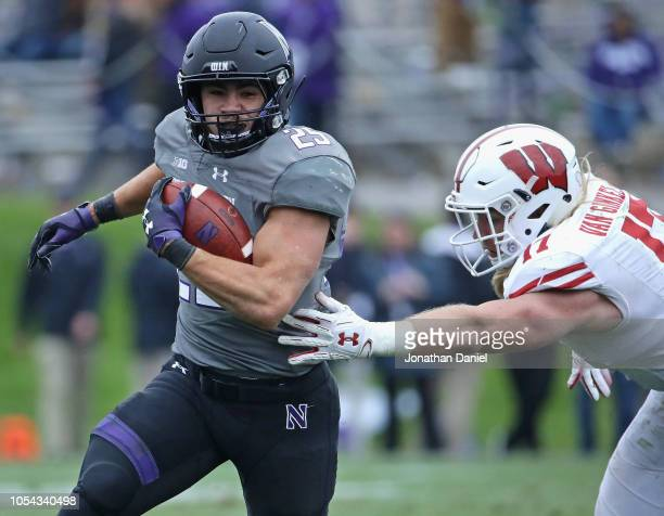 Isaiah Bowser of the Northwestern Wildcats breaks away from Andrew Van Ginkel of the Wisconsin Badgers for a first down at Ryan Field on October 27...