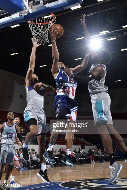 Isaiah Briscoe of the Lakeland Magic shoots against Isaiah Wilkins and Chinanu Onuaka of the Greensboro Swarm during the game on November 16 2018 at...