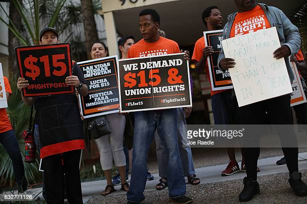 Isaiah Bryan Barfield holds a sign as he joins a protest against President Donald Trump's pick for Labor Secretary Andy Puzder outside the Miami...