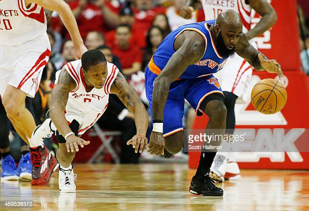 Isaiah Canaan of the Houston Rockets and Quincy Acy of the New York Knicks battle for a loose ball during their game at the Toyota Center on November...