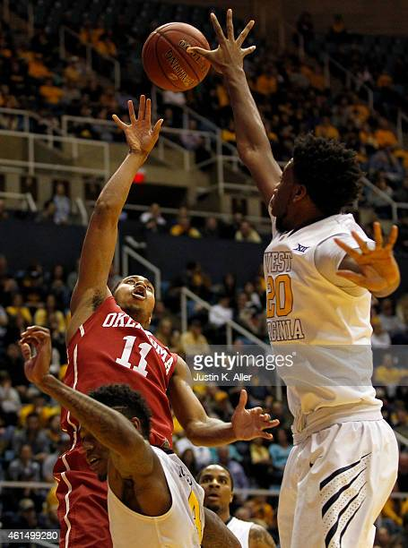 Isaiah Cousins of the Oklahoma Sooners drives to the basket against Brandon Watkins of the West Virginia Mountaineers during the game at the WVU...