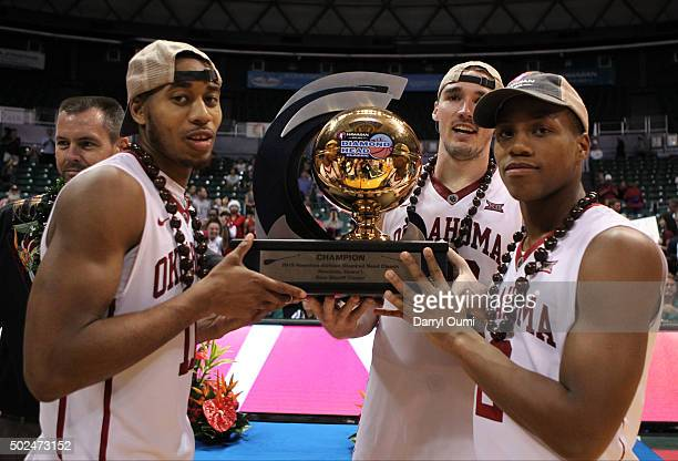 Isaiah Cousins Ryan Spangler and Dinjiyl Walker of the Oklahoma Sooners pose for a picture with the championship trophy after winning the Diamond...