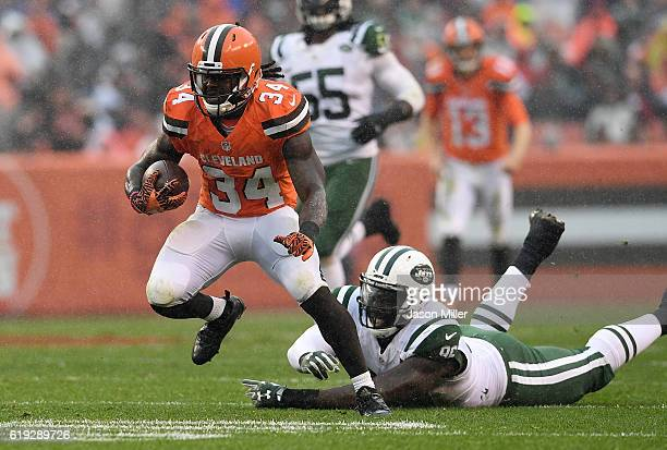 Isaiah Crowell of the Cleveland Browns carries the ball in front of a diving Muhammad Wilkerson of the New York Jets during the second quarter at...
