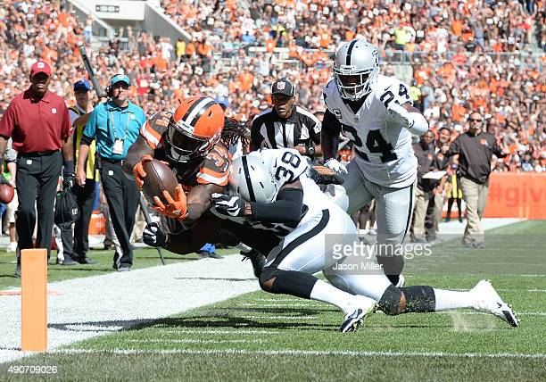 Isaiah Crowell of the Cleveland Browns is knocked out of bounds after picking up a first down by TJ Carrie in front of Charles Woodson of the Oakland...
