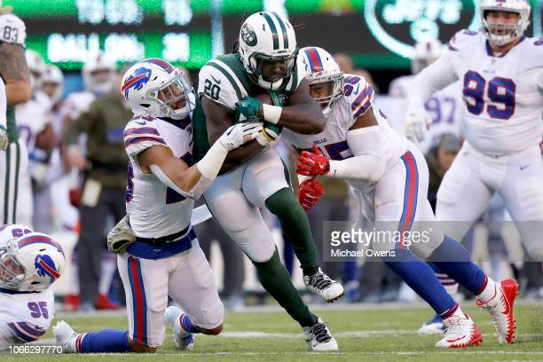 Isaiah Crowell of the New York Jets is tackled by Micah Hyde and Jerry Hughes of the Buffalo Bills during the third quarter at MetLife Stadium on...