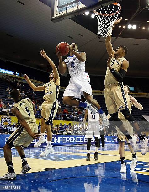 Isaiah Dennis of the Georgia State Panthers shoots over Curtis Diamond and Eric Ferguson of the Georgia Southern Eagles during the Sun Belt...