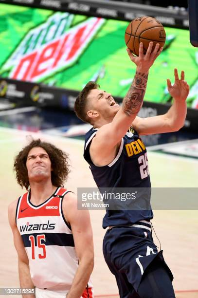 Isaiah Hartenstein of the Denver Nuggets goes up for a layup against Robin Lopez of the Washington Wizards during the first half at Capital One Arena...