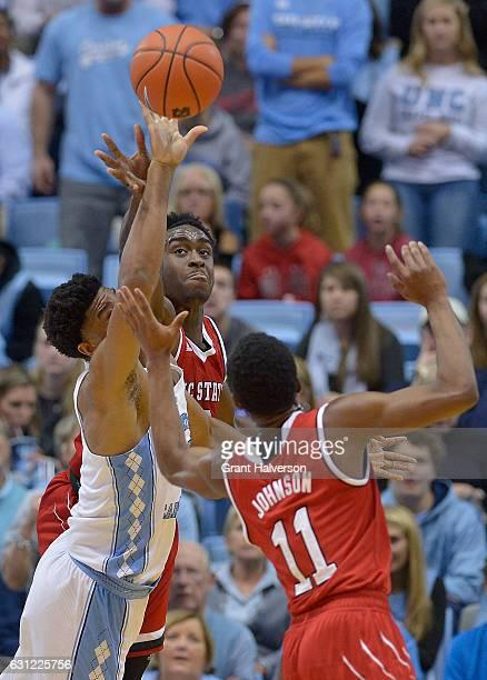 Isaiah Hicks of the North Carolina Tar Heels battles AbdulMalik Abu and Markell Johnson of the North Carolina State Wolfpack for a rebound during the...