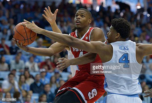 Isaiah Hicks of the North Carolina Tar Heels strips the ball away from Dennis Smith Jr #4 of the North Carolina State Wolfpack during the game at the...