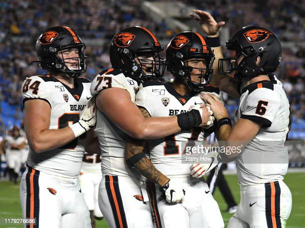 Isaiah Hodgins of the Oregon State Beavers celebrates his touchdown catch with Jake Luton Blake Brandel and Teagan Quitoriano to take a 273 lead over...