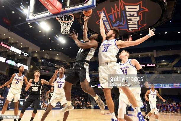 Isaiah Jackson of the Providence Friars tdrives tot he basket by Max Strus of the DePaul Blue Demons during a college basketball game at Wintrust...
