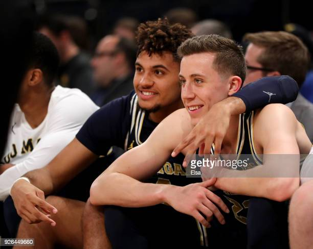 Isaiah Livers and Duncan Robinson of the Michigan Wolverines celebrate from the bench as they defeat the Nebraska Cornhuskers during quarterfinals of...