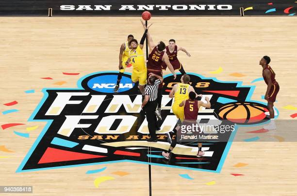 Isaiah Livers of the Michigan Wolverines and Cameron Krutwig of the Loyola Ramblers go up for the opening tip during the 2018 NCAA Men's Final Four...