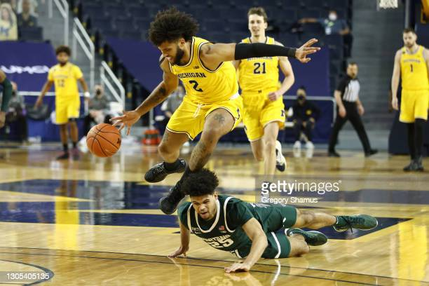 Isaiah Livers of the Michigan Wolverines battles for a loose ball against Malik Hall of the Michigan State Spartans during the second half at Crisler...