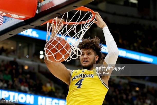 Isaiah Livers of the Michigan Wolverines dunks the ball in the first half against the Minnesota Golden Gophers during the semifinals of the Big Ten...