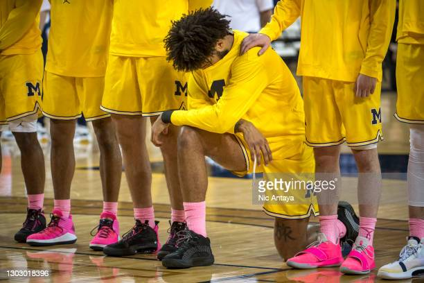 Isaiah Livers of the Michigan Wolverines takes a knee during the national anthem before the first half against the Rutgers Scarlet Knights at Crisler...