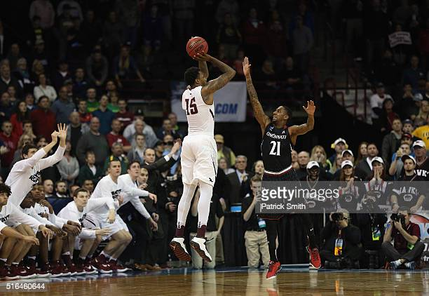 Isaiah Miles of the Saint Joseph's Hawks scores the gamewinning basket against Farad Cobb of the Cincinnati Bearcats in the second half during the...