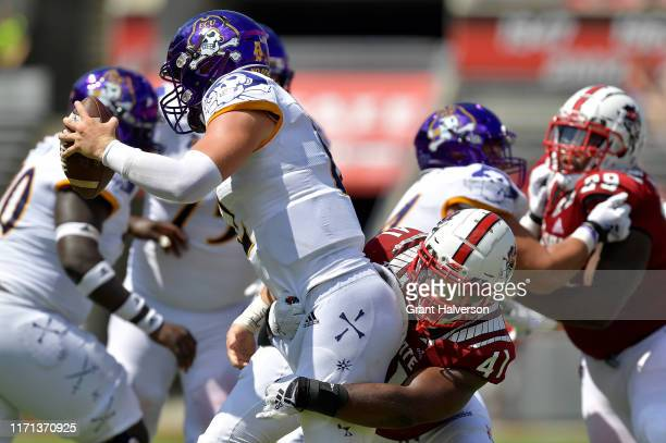 Isaiah Moore of the North Carolina State Wolfpack sacks Holton Ahlers of the East Carolina Pirates during the second half of their game at...