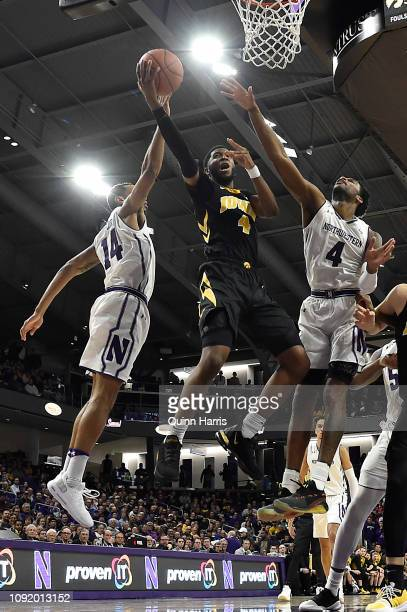 Isaiah Moss of the Iowa Hawkeyes shoots a layup against Ryan Taylor of the Northwestern Wildcats and Vic Law of the Northwestern Wildcats at...