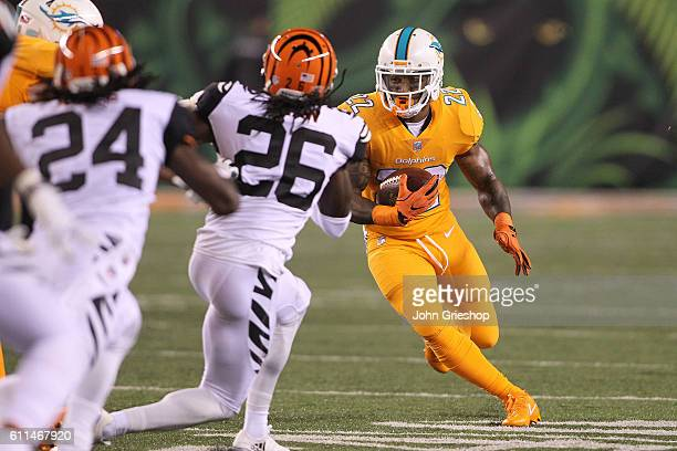 Isaiah Pead of the Miami Dolphins attempts to run the ball past Josh Shaw of the Cincinnati Bengals during the third quarter at Paul Brown Stadium on...