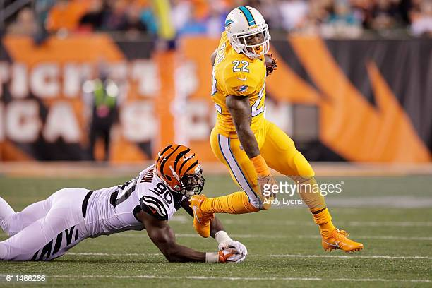 Isaiah Pead of the Miami Dolphins breaks a tackle by Michael Johnson of the Cincinnati Bengals during the second quarter at Paul Brown Stadium on...