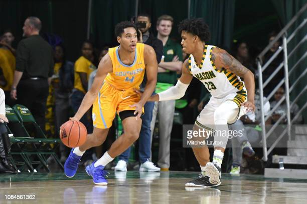 Isaiah Rollins of the Southern University Jaguars dribbles around Javon Greene of the George Mason Patriots during a college basketball game at the...