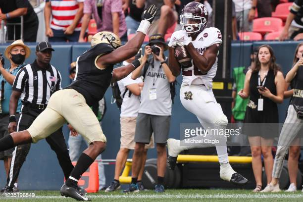 Isaiah Spiller of the Texas A&M Aggies catches the winning touchdown pass while being defended by Guy Thomas of the Colorado Buffaloes during the...