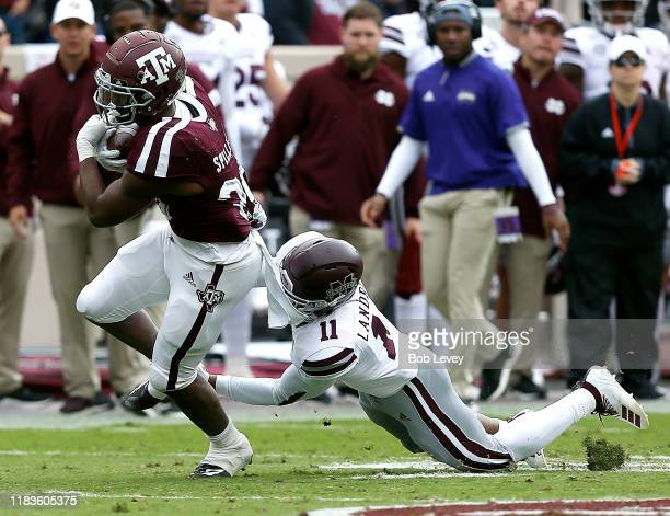 Isaiah Spiller of the Texas AM Aggies is tackled from behind by Jaquarius Landrews of the Mississippi State Bulldogs as he runs with the ball during...