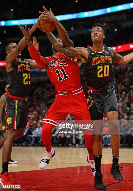 Isaiah Taylor and John Collins of the Atlanta Hawks knock the ball away from David Nwaba of the Chicago Bulls at the United Center on October 26 2017...