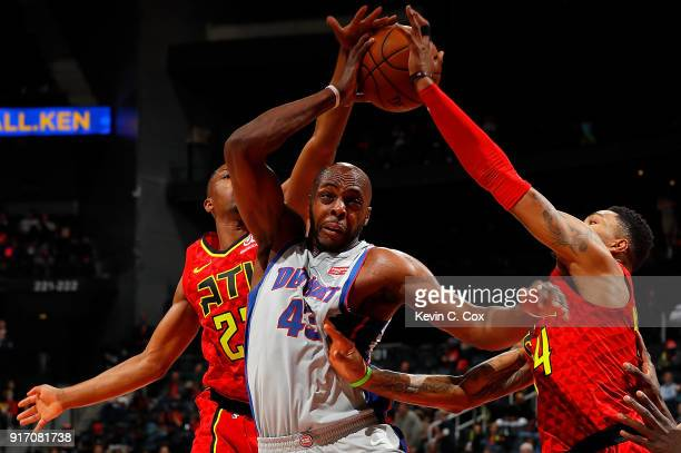 Isaiah Taylor and Kent Bazemore of the Atlanta Hawks defends against Anthony Tolliver of the Detroit Pistons at Philips Arena on February 11 2018 in...
