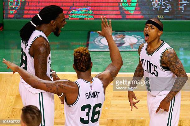 Isaiah Thomas of the Boston Celtics celebrates with Marcus Smart and Jae Crowder after hitting a three pointer during overtime of Game Four of the...