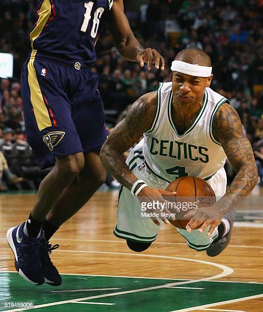 Isaiah Thomas of the Boston Celtics falls while driving against Toney Douglas of the New Orleans Pelicans during the third quarter at TD Garden on...