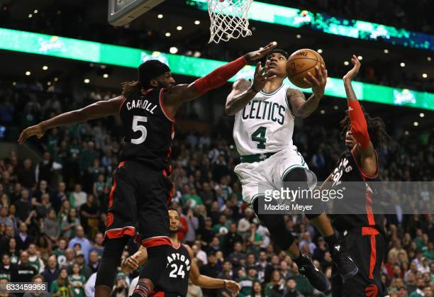 Isaiah Thomas of the Boston Celtics takes a shot against DeMarre Carroll of the Toronto Raptors and Lucas Nogueira during the fourth quarter at TD...