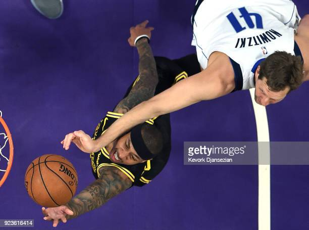 Isaiah Thomas of the Los Angeles Lakers is hit on the face by Dirk Nowitzki of the Dallas Mavericks as he scores a basket during the first half at...