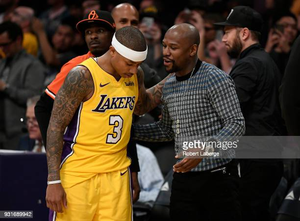 Isaiah Thomas of the Los Angeles Lakers talks to retired boxer Floyd Mayweather after the game against the Denver Nuggets on March 13 2018 at STAPLES...