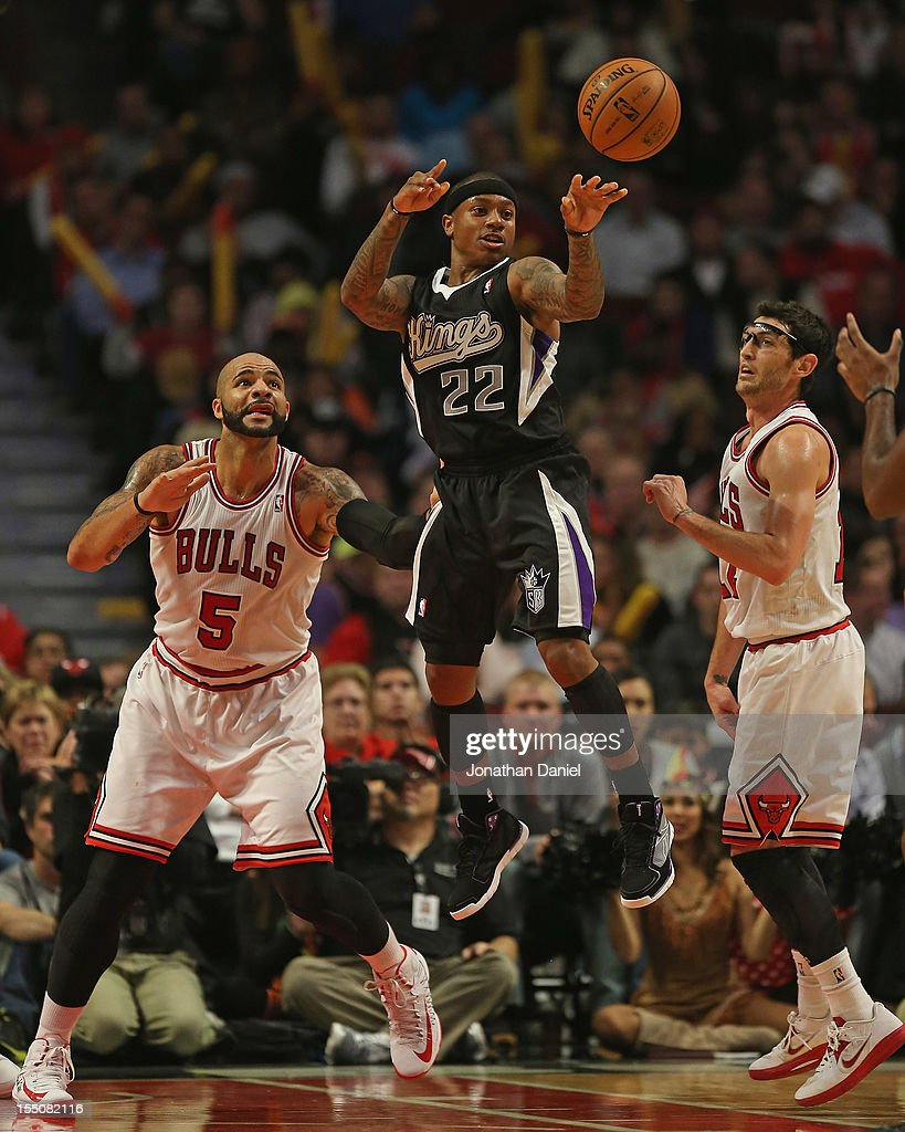 Isaiah Thomas #22 of the Sacramento Kings passes between Carlos Boozer #5 and Kirk Hinrich #12 of the Chicago Bulls at the United Center on October 31, 2012 in Chicago, Illinois. The Bulls defeated the Kings 93-87.