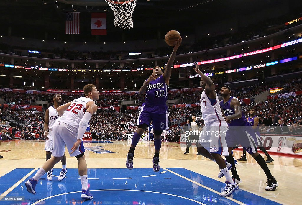 Isaiah Thomas #22 of the Sacramento Kings shoots over Blake Griffin #32 and Lamar Odom #7 of the Los Angeles Clippers at Staples Center on December 21, 2012 in Los Angeles, California. The Clippers won 97-85.
