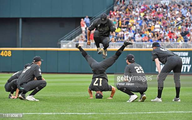Isaiah Thomas of the Vanderbilt Commodores jumps through the legs of teammate Walker Grisanti in between innings against the Michigan Wolverines...