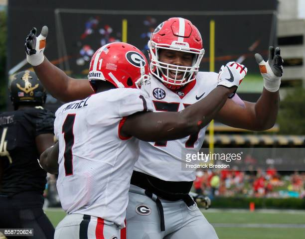 Isaiah Wynn of the Georgia Bulldogs congratulates teammate Sony Michel on scoring a touchdown against the Vanderbilt Commodores during the second...