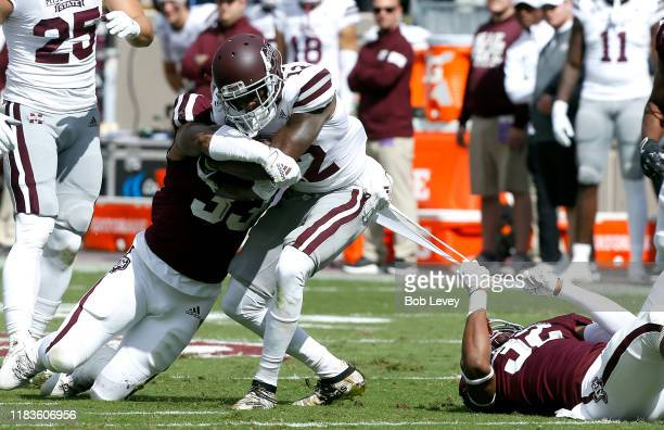 Isaiah Zuber of the Mississippi State Bulldogs is tackled by Andre White Jr #32 of the Texas AM Aggies and Aaron Hansford during the second quarter...